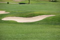 Sand trap or bunker on a golf course curving in the middle of manicured green acting as hazard and penalty for golfers during Royalty Free Stock Images