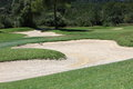 Sand trap or bunker on a manicured fairway on a golf course designed as a hazard and penalty for the player Royalty Free Stock Photography