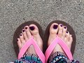 Sandal, Close Up on Girl`s Violet Nail and Feet Wearing Pink Sandals on the Street Background Royalty Free Stock Photo