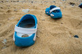 Sandals leaving the beach sand blue ribbon going away from Royalty Free Stock Photos