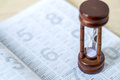 Sandglass on calendar timing of diary table Stock Photos