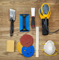 Sanding and painting accessories on faded wooden boards overhead view of equipment positioned rustic items include electric sander Stock Photo