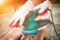 Sanding a wood with orbital sander Royalty Free Stock Photo