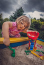 Sandpit fun girl playing in the in the home garden Royalty Free Stock Photos