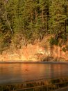 Sandstone cliff in sunset light, reflections in water Royalty Free Stock Photo