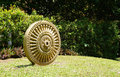 Sandstone craving dhamma wheel the elevation detail of the on the grass with plant background under the sunlight Royalty Free Stock Images