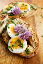 Sandwich with adition of mackerel fish , eggs and edible flowers of chives on wooden table Royalty Free Stock Photo