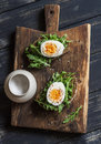 Sandwich with arugula, boiled egg and mustard on a wooden board. Royalty Free Stock Photo