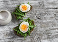 Sandwich with arugula and boiled egg on a wooden board. Healthy breakfast Royalty Free Stock Photo