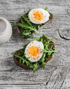 Sandwich with arugula and boiled egg on a wooden board. Royalty Free Stock Photo