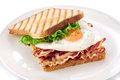 Sandwich with bacon, fried egg and lettuce on a plate. Royalty Free Stock Photo