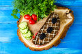 Sandwich bread and tomato cucumber blackberry parsley and dil dill on a tree stump on a blue background Stock Image