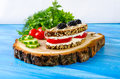 Sandwich bread and tomato cucumber blackberry parsley and dil dill on a tree stump on a blue background Royalty Free Stock Images
