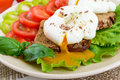 Sandwich with egg poached, lettuce, black bread with seeds, tomatoes, sweet pepper on a plate on a white wooden table. Royalty Free Stock Photo