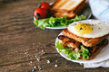 Sandwich with eggs, chicken, cucumber and lettuce on a wooden background. Selective focus. copy space Royalty Free Stock Photo