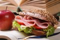 Sandwich with ham and vegetables and red apple on open notebook Royalty Free Stock Photo