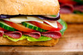 Sandwich with lettuce, slices of fresh tomatoes, cucumber, red onion, salami and cheese Royalty Free Stock Photo