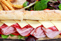 Sandwich with lettuce, slices of fresh tomatoes, salami, hum, cheese Royalty Free Stock Photo