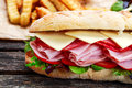 Sandwich with lettuce, slices fresh tomatoes, salami, hum and cheese Royalty Free Stock Photo