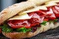 Sandwich with lettuce, slices of fresh tomatoes, salami, hum and cheese. Royalty Free Stock Photo