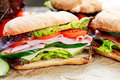 Sandwich with lettuce, tomatoes, cucumber, red onion, salami, ham, cheese Royalty Free Stock Photo