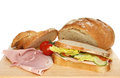 Sandwich and loaf closeup of a freshly baked bloomer with ham tomatoes on a wooden board Stock Images