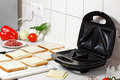 Sandwich maker toasts and vegetables on the table Stock Images