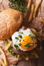 Sandwich with meat, a fried egg and fries close-up. vertical top Royalty Free Stock Photo