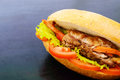 Sandwich: Meat rolls with vegetables in a bun with tomato and lettuce leaves Royalty Free Stock Photo