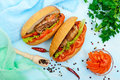 Sandwich: Meat rolls with vegetables in a bun with tomato and lettuce leaves. Royalty Free Stock Photo