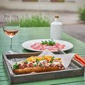Sandwich with baguette and meat on a background of a green table and a glass of pink wine and prosciutto. italian fast Royalty Free Stock Photo
