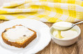 Sandwich from muffin and spoon with condensed milk above bowl Royalty Free Stock Photo