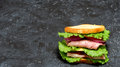 Sandwich over spotty black double of bread ham cheese tomato cucumber onion and lettuce on grey background Royalty Free Stock Photography