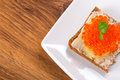 Sandwich with red caviar on the plate Stock Photography