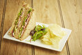 Sandwich with salad and potato chips on white dish wooden table top Stock Photo