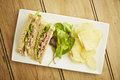Sandwich with salad and potato chips on white dish wooden table top Stock Photography