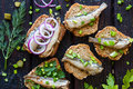 Sandwich with sardines sprinkle with onions on a black background closeup Royalty Free Stock Photography