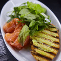 Sandwich with smoked salmon, cheese, tomatoes and herbs for healthy breakfast. close up Royalty Free Stock Photo