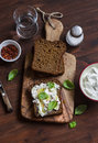 Sandwich with soft cheese, olive oil and basil, served on olive cutting board on dark wooden surface. Healthy Breakfast Royalty Free Stock Photo
