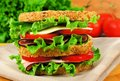 Sandwich still life large ham lettuce and tomato on whole grain bread Royalty Free Stock Image