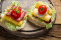 Sandwich with tomato cocktail cheese and lettuce on old wooden cutting board Stock Photos