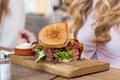 Sandwich on wooden plate with women in background closeup of Stock Photography