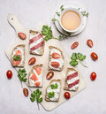 Sandwiches with cheese, herbs and red fish, lunch with green tea with thyme wooden rustic background top view close up Royalty Free Stock Photo
