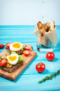 Sandwiches with olive, quail eggs, cherry tomatoes and potatoes on a wooden blueboard. Royalty Free Stock Photo