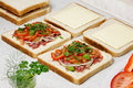 Sandwiches preparation and vegetables on the table Royalty Free Stock Images