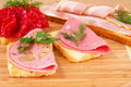 Sandwiches with salami bacon and mortadella on wooden board Stock Photos