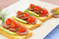 Sandwiches with salami cheese cherry tomato and dill on plate Stock Photo