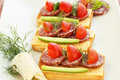 Sandwiches with salami cheese cherry tomato and dill on plate Stock Photography