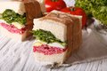 Sandwiches with salami wrapped in paper close-up horizontal Royalty Free Stock Photo
