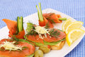 Sandwiches with salmon cheese lettuce herbs on plate olives and lemons Stock Photo